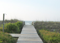 an outdoor shower along a boardwalk leading to the beach